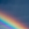 A street lamp, a rainbow and dark clouds.  Depth of Field.