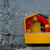 A weathered life saving ring bouy sits against a grey cement marina wall.