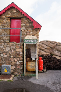 Traditional Irish phone box beside a heap of bo