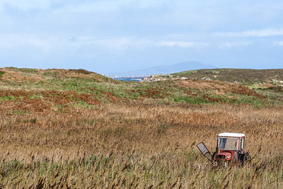 A lone abandoned red tractor sits alone in tall grass in county Donegal, Ireland.