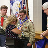 Twin brothers Adam, left and Benjamin Chidester, of Townsend, are awarded the rank of Eagle Scout, following their five older brothers, at a ceremony at Littleton Chapel in Littleton. Their mother Laura Chidester fastens the blue neckerchiefs worn by Eagle Scouts, rolled up by Duncan Graham of Groton, District Commissioner for the Massasoit District of Nashua Valley. (SUN/Julia Malakie)