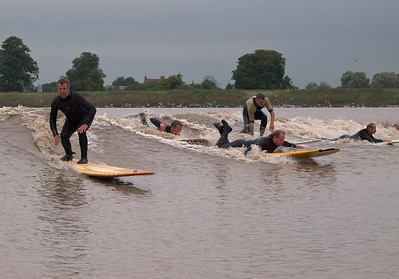 Steve King riding the wave with other surfers alongside.