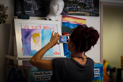 A girl takes a picture of a painting with her iPhone during a art class in San Diego.
