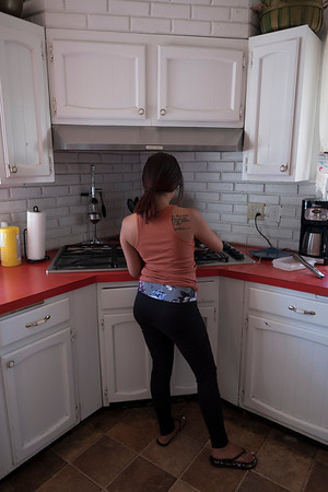One of the young ladies fixes her lunch in the kitchen.