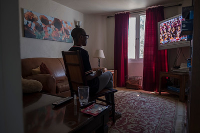 A young woman, a resident of GenerateHope, watches a college football game on a Saturday afternoon.