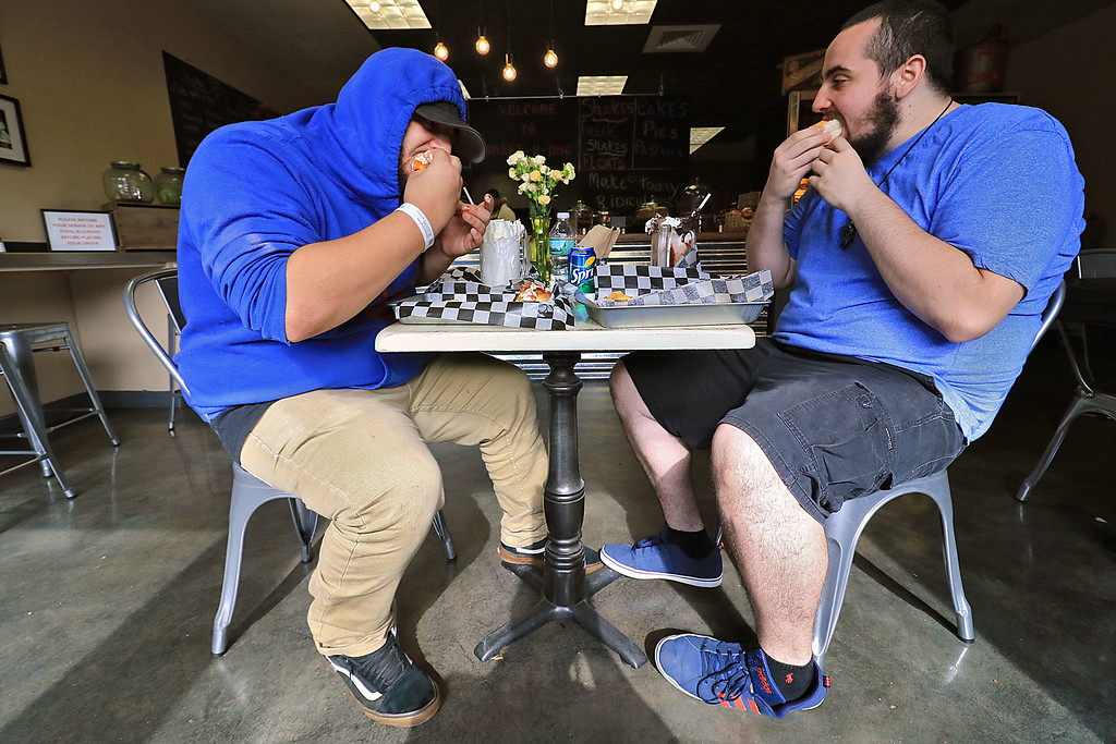 . A new restaurant called Shake-N-Dog has opened in Leominster that serves up hot dogs and shakes. Enjoying their lunch on Thursday is Mateo Fartado, 21, and Shawn Bianchin, 21, both of Leominster. SENTINEL & ENTERPRISE/JOHN LOVE