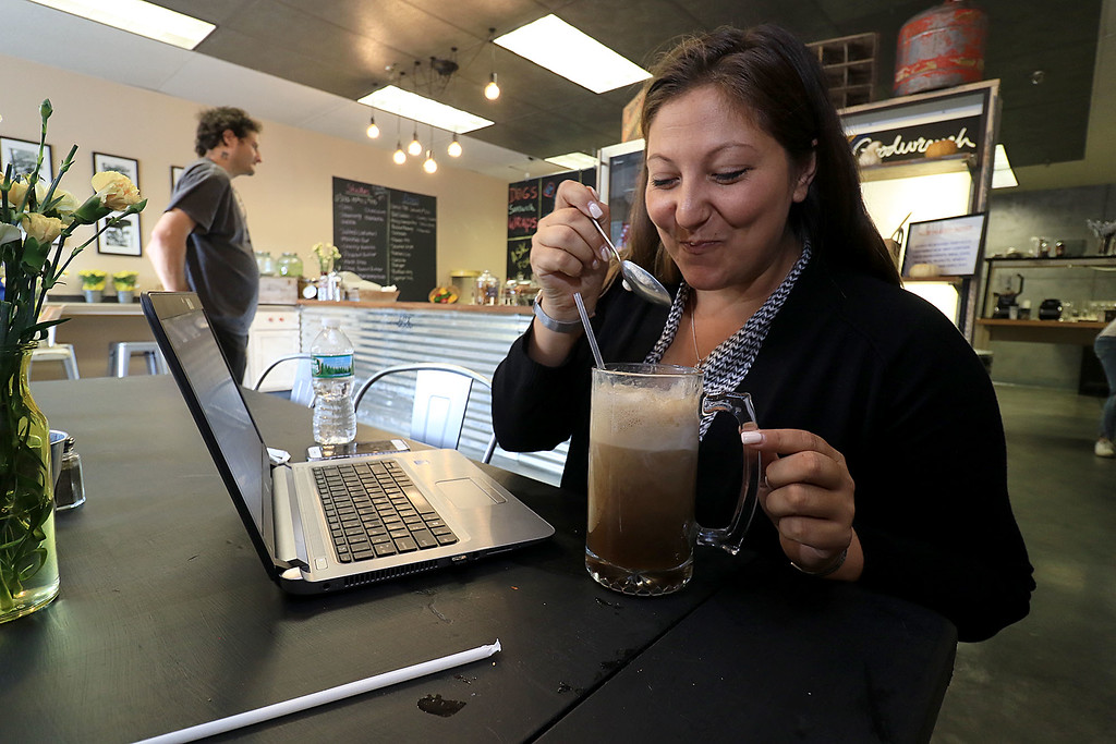 . A new restaurant called Shake-N-Dog has opened in Leominster that serves up hot dogs and shakes. Nicole Rendon of Leominster tries a root beer float with her hotdogs during her lunch break on Thursday. SENTINEL & ENTERPRISE/JOHN LOVE