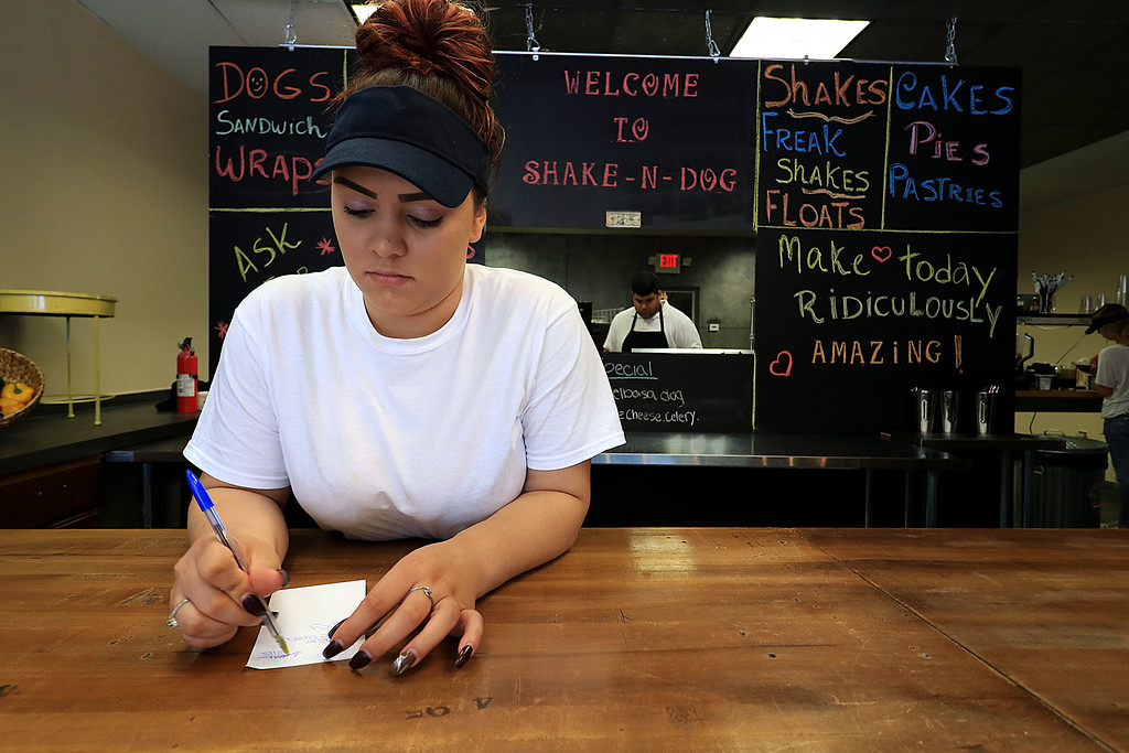 . A new restaurant called Shake-N-Dog has opened in Leominster that serves up hot dogs and shakes. Employee Adrianna Gonzalez, 20, waits for customers on Thursday in the restaurant. SENTINEL & ENTERPRISE/JOHN LOVE