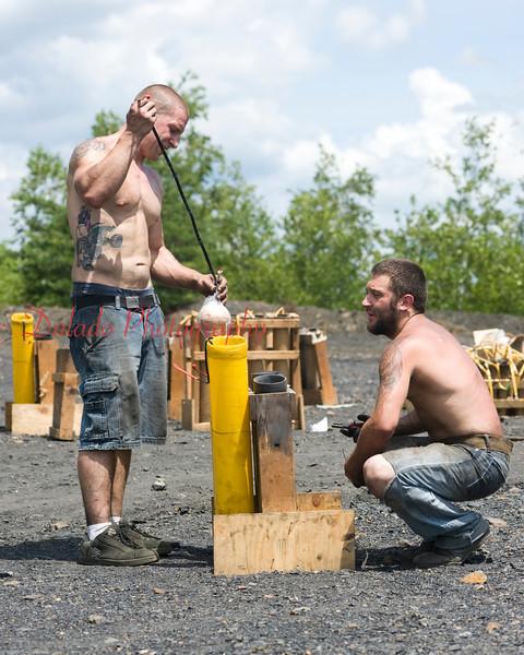Brian Knarr, left, and Michael Fuller loads a firework shell.