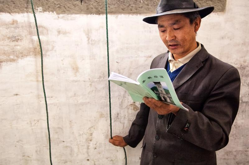 Tibétain chrétien de Cizhong sonnant les cloches de l'église du village pour la messe dominicale. Province du Yunnan/Chine