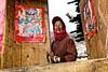 Une villageoise tibétaine à l'entrée de sa maison placardée d'affiches du Nouvel An chinois. Province du Yunnan/Chine