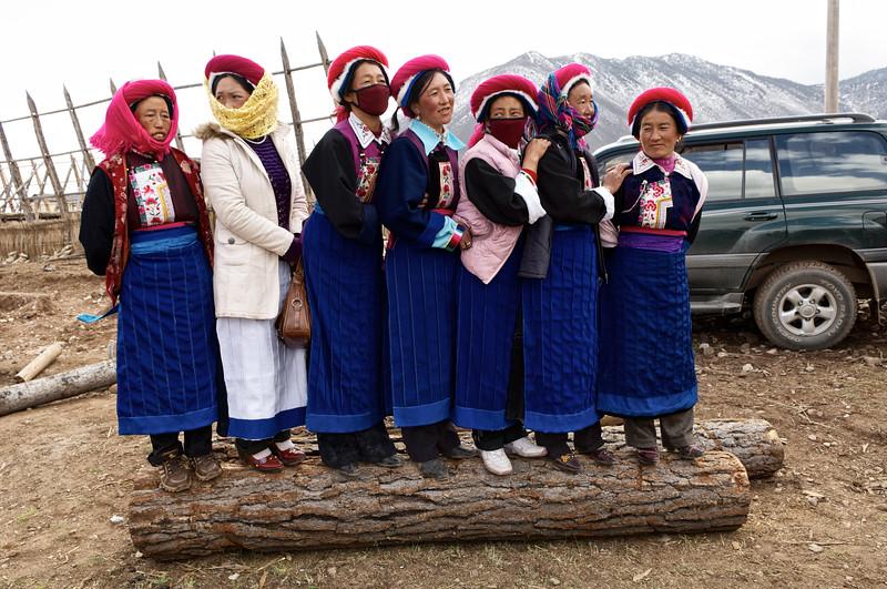 """Femmes tibétaines montées sur un tronc pour mieux voir le déroulement de la cérémonie d'un mariage dans une ferme de la périphérie de Zhongdian (renommée """"Shangri-La""""). Province du Yunnan/Chine"""