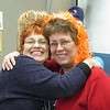 """Staff members, Sandy Brownlee and Cathy Sunshine, showing off their new """"doos""""."""
