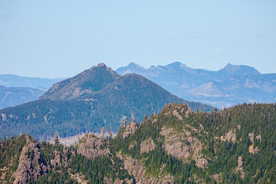 The peaks and ridges of the Cannon Beach peaks as seen from the top of Indian Chieftain. Sugarloaf peak is the most prominent with Onion Peak ridge in the foreground and Saddle Mountain and Humbug Peak visible in the background.