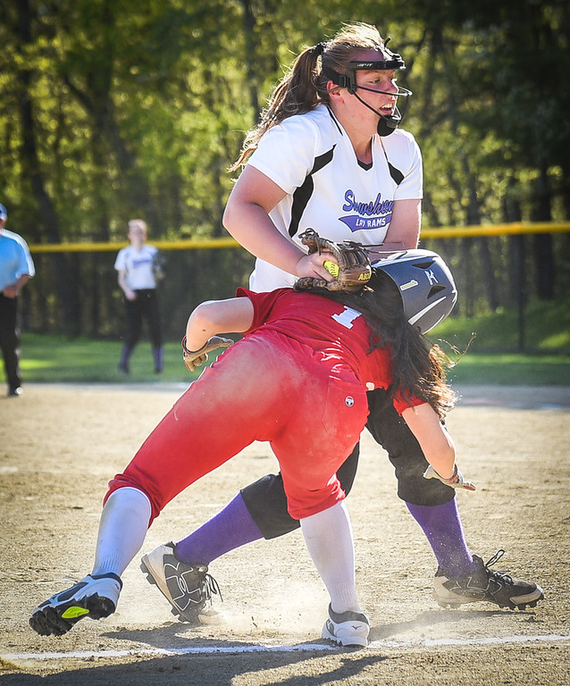 . Innovation Academy\'s Yanessa Rowe, bottom in red, gets caught up in the middle of third base and home steal, getting tagged out by Shawsheen\'s third base, Katelyn Logue, during Monday\'s game at the Billerica field.  Photo:  SUN/Scot Langdon