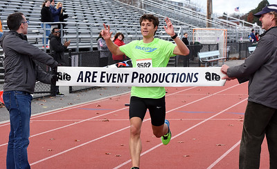 STAN HIUDY - SHUDY@DIGITALFIRSTMEDIA.COM Shenendehowa graduate Scott Mindel breaks the tape as the overall winner and new course record holder at the Shenendehowa Veteran's Day Dash on the Clifton Park campus Friday morning.