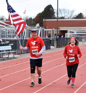 STAN HUDY - SHUDY@DIGITALFIRSTMEDIA.COM 20-year U.S. Navy veteran Gary Washock of Troy carries an American Flag, running alongside Marcia Rice as they head towards the finish line of Friday's annual Shenendehowa Veteran's Day Dash 5k on the Clifton Park campus.