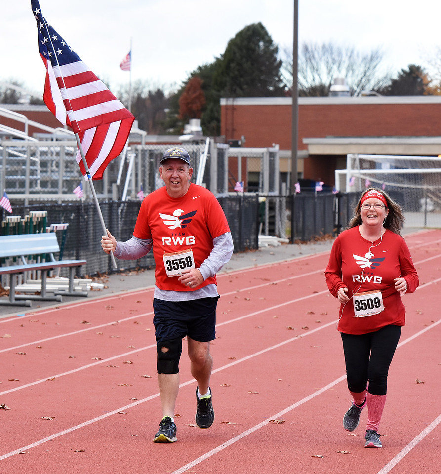 STAN HUDY - SHUDY@DIGITALFIRSTMEDIA.COM20-year U.S. Navy veteran Gary Washock of Troy carries an American Flag, running alongside Marcia Rice as they head towards the finish line of Friday's annual Shenendehowa Veteran's Day Dash 5k on the Clifton Park campus.