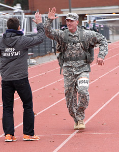 STAN HUDY - SHUDY@DIGITALFIRSTMEDIA.COM U.S. National Guard Sargent First Class Douglas Kirsch gets a high-five from Albany Running Exchange president and Shenendehowa Veteran's Day Dash 5k announcer Josh Merlis as he heads towards the finish line on Veteran's Day at the Shenendehowa High School Campus, Nov. 11, 2016.