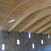 The roof of the fellowship hall is glu lam-arches bearing directly on the concrete tilt-wall slabs, with exposed wood deck.