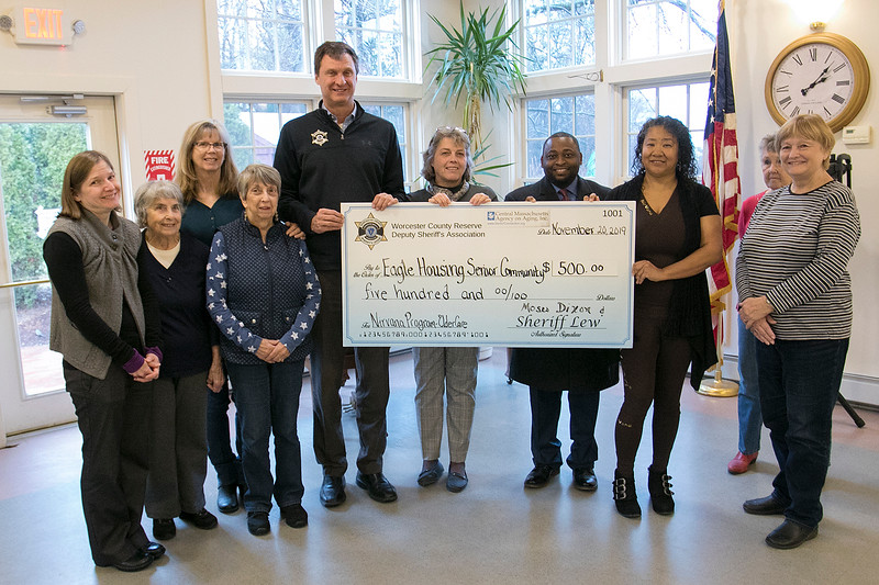Sheriff Lew Evangelidis in partnership with Central Mass Agency on Aging present a Grant Award to the Senior Center at the Eagle House in Lunenburg Wednesday, Nov. 20, 2019. The five-hundred dollar grant award will be used to support their Nirvana Program for Seniors which provides Breathing and Meditation Classes. The funds were raised at the Sheriff's joint collaboration ElderCare 2019 event held in May. ElderCare is an educational day for seniors whose proceeds go onto benefit senior programs throughout Worcester County. Holding the check, from left is Shireff Evangelidis, Director of the Senior Center Susan Doherty, Executive Director/CEO CMAoA Moses Dixon and the instructor for the Nirvana Program Carolyn Sargent. Surrounding them are members of the center. SENTINEL & ENTERPRISE/JOHN LOVE