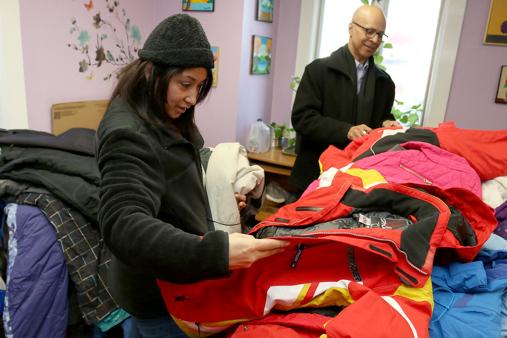 . Worcester County Sheriff Lewis G. Evangelidis was at the Spanish American Center in Leominster on Monday to drop off over 1,000 winter coats. Leominster\'s Warmer Winters hand made hats and gloves for the sheriff to add to his coats to give out at the center as well. Karina Rodriguez picks out a coat at the center on Monday. SENTIENL & ENTERPRISE/JOHN LOVE