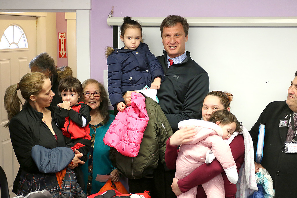 . Worcester County Sheriff Lewis G. Evangelidis was at the Spanish American Center in Leominster on Monday to drop off over 1,000 winter coats. Leominster\'s Warmer Winters hand made hats and gloves for the sheriff to add to his coats to give out at the center as well. Sheriff Evangelidis  talks about his coat drive as he holds Karina Ramos, 4, during his visit to drop of the coats at the center. SENTIENL & ENTERPRISE/JOHN LOVE