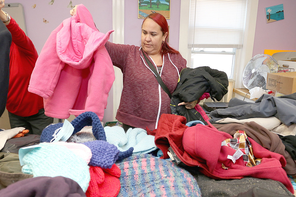 . Worcester County Sheriff Lewis G. Evangelidis was at the Spanish American Center in Leominster on Monday to drop off over 1,000 winter coats. Leominster\'s Warmer Winters hand made hats and gloves for the sheriff to add to his coats to give out at the center as well. Carmen Rodriguez looks through the coats for one her size at the center. SENTIENL & ENTERPRISE/JOHN LOVE