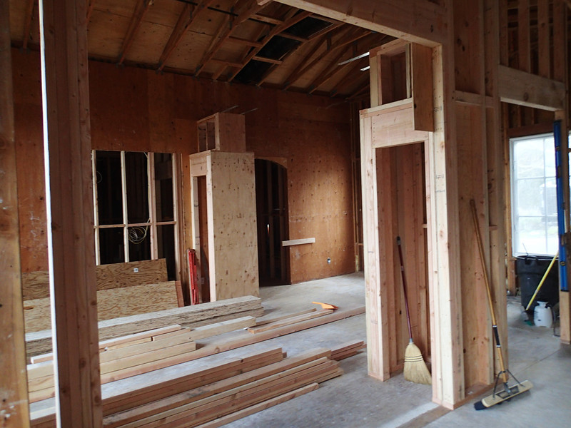 """View from the """"kitchen nook"""" into the living room/foyer through the framing of the new opening that will be an arch - those are the new column bases, with the arch being constructed on top."""