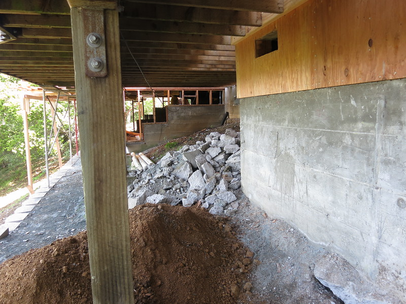 """You can see all the way through the crawl space underneat the master bedroom. The concrete rubble is what is left of the old chimney """"Foundation""""."""