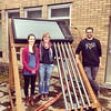 Becca, Caitlin, and Kyle with the hybrid solar collector on the roof of Shiley Hall.