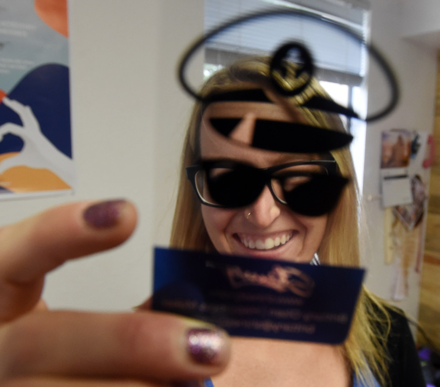 """. \""""Happiness Maker,\"""" Brittany Olsen, has business cards that can be positioned to make her look like she is wearing a cap and sunglasses. Shinesty in Boulder have fun with their job titles. \""""Creative\"""" job titles in Boulder County is on the rise, say job coaches and HR professionals. Cliff Grassmick  Photographer  May 11,  2018"""