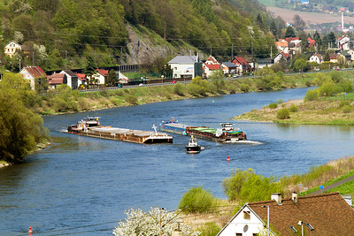 Barge ALESSANDRO heads down stream as Barge CSPL TR15 has tug assistance through the current heading up stream towards the lock system at Strekov on the River Elbe passing Techlovice, Czech Republic. 21st April 2016.