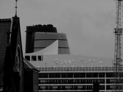 The funnel of the Queen Mary 2 with it's illuminated nameplates lit up as the light was starting to fail. The building to the left is St. Mary's Church, showing how big the boat is itself as St. Mary's is no small building!