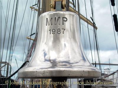 Ships Bell - MIR during a visit to Birkenhead - June 19, 2004.   STS MIR (Russian: Мир, meaning World or Peace) is a three-masted, full rigged Sail Training Ship, based in St. Petersburg, Russia. She was built in 1987 at the Lenin Shipyard in Gdańsk, Poland.  MIR is the second largest of six sister ships designed by Zygmunt Choreń and weighs 2,385 tonnes. She is 109.2 metres long, with a beam of 13.9 m and a draught of 6.3 m. The main mast is 52 m high and along with the other masts supports a total sail area of 2,771 m2.  Her sister ships are Dar Młodzieży, Druzhba, Pallada, Khersones and Nadezhda. Mir is 8 m shorter than the longest current sailing ship, the Sedov (117.5 m).