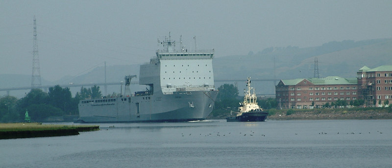 Serious contract timescale and cost overruns were experienced with the first two Bay Class ships, constructed at Swan Hunter Shipbuilders at Wallsend on Tyneside. By mid 2006 Largs Bay had been completed but Lyme Bay was still far from completion despite having been originally due for delivery in 2005. With total contract costs at Swan Hunter exceeding £300m compared to approximately £180m for the two ships built by BAE Systems at Govan, the Ministry of Defence decided to cancel the contract with Swan Hunter and invited BAE Systems to complete RFA Lyme Bay. In Mid July, the partly completed Lyme Bay was towed out of the Tyne by the large Switzer tug Ormesby Cross - marking the saddest possiible end to two centuries of illustrious shipbuilding on the River Tyne, which arguably, had been the greatest rival to the Clyde in the era when Britain dominated world shipbuilding. The tow around the coast of Scotland and through the Hebrides took several days and by the morning of Saturday 23rd July 2006, Ormesby Cross was towing her large charge up the Clyde to Scotstoun. In this view we see the two vessels at the famous Dalmuir Bend with Newshot Isle on the left. The buildings on the right occupy the site of another former famous shipyard - the huge Dalmuir Naval Construction Works of William Beardmore & Co which had opened a century earlier in 1905. It had been built to specialise in large naval ships, such as battleships, but enjoyed only a few years of success being severely effected by the terms of the Washington Treaty that was signed after World War I.