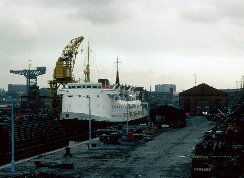A more distant view of motor vessel Lady of Mann in Govan Drydock No 3. The yellow crane to the left of the vessel was one of two (by then) listed engineering structures built by the world famous Glasgow structural engineering firm Sir William Arrol of Dalmarnock Ironworks and Parkhead Crane Works.The twin listed cranes were subsequently destroyed without permission later in the 1980s. The large cantilever crane to the left of the picture is the now famous 'Finnieston Crane' (although it should properly be referred to as the Stobcross Crane). This type of giant cantilever crane was a major product of Arrols for many years. Although the Glasgow firm supplied a significant proportion of the 60-or-so structures of this type built around the world, the 'Finnieston Crane' was actually built by the Carlisle-based Cowans Sheldon company (Arrol did construct the deep foundations for the crane). Less than 20 of these structures survive worldwide now (in 2006), five of the survivors being on Clydeside.