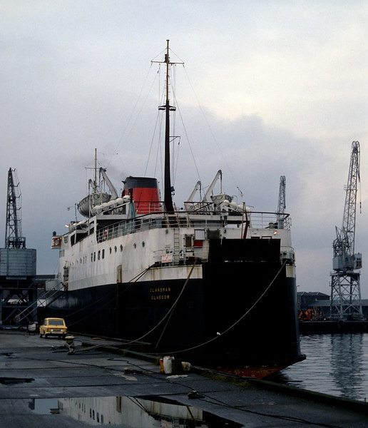Clansman and her original sister vessels, Hebrides and Columba, had been built in 1963-64 at the Hall Russell shipyard in Aberdeen to the order of the Secretary of State for Scotland. They were chatered to David MacBrayne to introduce new car carrying services to the Inner and Outer Hebrides. They bore traditional West Coast names and the MacBrayne livery but, while owned by the Scottish Secretary, they were registered in Leith. Their port of registry was changed to Glasgow when the ownership of the vessels was transferred to Caledonian MacBrayne as part of the State-owned Scottish Transport Group in the 1970s.<br /> <br /> In this picture a Linwood-built Hillman Imp car can be seen alongside Clansman, as can a wooden-cabbed quayside crane, also built in Renfrewshire, in its case by the giant engineering company Babcock & Wilcox of Renfrew.
