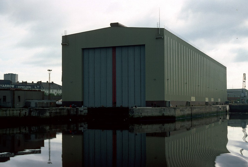 During the late 1970s Yarrow (Shipbuilders)Ltd build a huge covered refitting hall over the No 2 Elderslie Drydock. It is seen here in 1982 when still relatively new. The first two drydocks at Elderslie had been built around 1907 to accommodate the ship repair business of John Shearer which had been displaced from its former Kelvinhaugh Slip Dock to enable the construction of new port wharfage (Yorkhill Quay). A third drydock was added in the 1960s. All three drydocks remain serviceable in 2006 although, in general, over the last 25 years the two 'open' drydocks seem to have been utilised more than the covered dock.