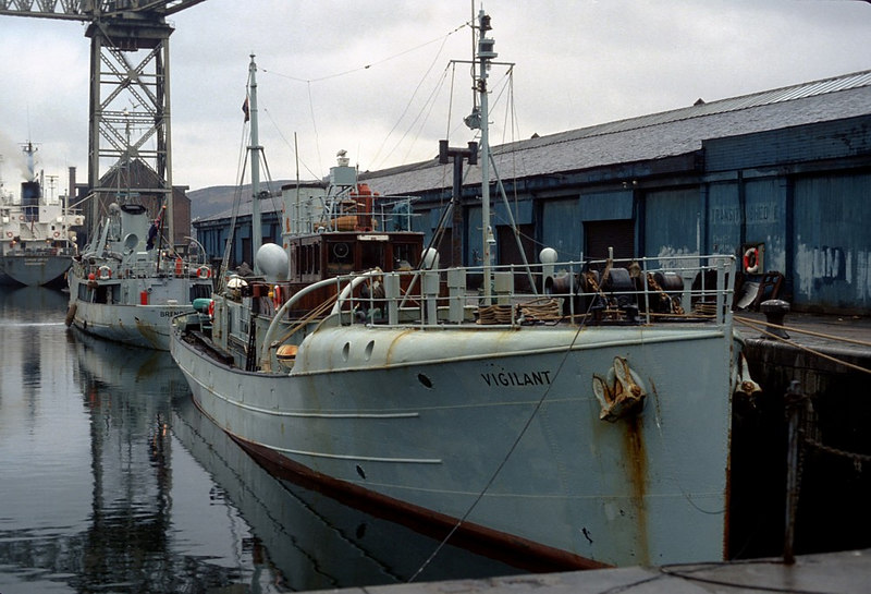 Shown berthed astern of the cutter Brenda (Denny's YN 1453) in James Watt Dock that day in 1982 is the former fisheries cutter Vigilant. Originally built by Denny at Dumbarton (yard No 1280) in 1935 with the appearance of a steam trawler, the vessel had a taller funnel, smaller wheelhouse and shorter whaleback fo'c'stle. She was the third vessel to bear the name Vigilant in the Scottish fisheries protection service. Special attention was given to the elimination of vibration. It was proposed to use electrical welding in her construction but it is not confirmed whether that took place. The price was £35,800 however there was a penalty of £5 per day for late delivery. She was delivered on 17 Jan 1936 against a contract delivery of 20 December 1935 but it is not known if the £140 penalty was exercised. Although looking basically like a Scottish west coast trawler in her orginal form she had finer lines giving her a maximum speed of 15 knots. Various devices were fitted to allow her to masquerade as a commercial fishing boat including grooves in her hull plating to enable false name boards to be fitted, canvas could be rigged to vary (apparently) the gap between the funnel and wheelhouse, the heights of the original funnel and the topmasts could be varied dummy gallows were carried and the square step at the bow could be varied with a rounded board. It has to be stated, however, that none of this camouflage worked particularly well and it was not repeated in subsequent vessels (info The Denny List Part IV) During WW2 she served initially as an examination vessel in the Clyde and later as an accommodation ship at the Campbeltown tug base, renamed Ixion. Later still she was moved to Larne for target towing. In 1945 she moved to Portsmouth as a reserve and. the following April. was designated for 'special service' in the Nore Channel. She resumed civilian service as Vigilant in December 1947. In 1980 she was officially named Vigilant II to free her name for her replacement, the fourth Vigilant, launched at the Ferguson yard in Port Glasgow and fitting out just upriver of the Watt Dock in Lithgow's Kingston Basin during 1982. The venerable craft was sold to Panama registered Sheridan Trading and renamed Vigilant, thus for a short spell there seemed to be two vessels bearing the same name on the Clyde. <br /> <br /> Note her prominent black painted galley chimney, a reminder of the days of coal fired cooking ranges at sea