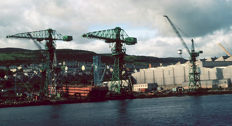 "Scott Lithgow's Kingston shpyard at Port Glasgow which, in 1982, was building 3 semi-submersible barged to facilitate the assembly of the deck module onto the jacket of the semi-submersible drilling platform Sea Explorer (corrected identity),building at Cartsburn.<br /> <br /> Correction and additional information courtesy of Tom Carreyette -<br /> <br /> ""The barges SLB1, 2 & 3 were for the load out of deck module for semi-submersible drilling rig SEA EXPLORER. The pontoons & columns launched from Cartsburn (seen in the next picture) were ballasted down at The Hole (deep part of Tail o' the Bank) and the deck floated over on these 3 barges for 'mating'. OCEAN ALLIANCE was a different semi-sub built and launched in one piece from the Glen Yard, under the Goliath crane."""