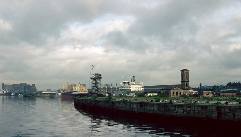 View downstream during the canting along a section of Stobcross Quay, where dockside sheds had already been removed, to Yorkhill Quay. The two vessels berthed there (Orfeo and Albertwil) were also on long term lay-up - they are re-visited later in this gallery, Between them stands the (by then) derelect river and dock Control Tower and Semaphore Signaling Tower formerly operated by the Clyde Navigation Trust when this section of the River Clyde was amass with ships from around the globe. To the right is the sandstone tower and enginehouse of the former Queens Dock Hydraulic Pumping Station. The powerful steam engines there had forced water into a massive accumulator tank (in the tower) which was fitted with a heavy weight to maintain the hydraulic pressure. High pressure water was conveyed by hundreds of miles of cast pipes around the quays of the very large twin-basin Queens Dock  where it was used to power many large cranes and other dockside equipment. Hydraulic power from the pumphouse was also used to slew the heavy swing bridge that once spanned the entrance to the Dock (adjacent to the site now occupied by the Glasgow City Heliport). Subsequently, the pumphouse became an upmarket restaurant but it failed after a relatively short time. It is now accociated with the nearby 'Tall Ship', the Port Glasgow-built barque Glenlee of 1896. <br /> <br /> In the distance in the picture can be seen the still operational (in 1982) Meadowside Granary with a vessel alongside Meadowside Quay.