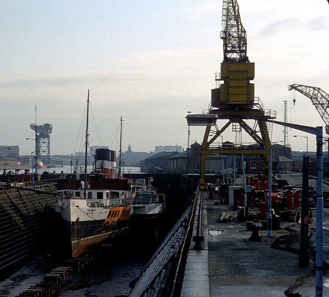 During the early spring of 1982, in preparation for her first sailing of the season at Easter, Waverley steamed the short distance from her lay-up berth at Stobcross Quay (ahead of Sound of Islay seen in the background of this picture) to be stemmed into the No 2 Graving Dock at Govan. Here we see her sitting on the blocks in the dock undergoing lower hull survey abd repair.<br /> <br /> Note how navigation of the River Clyde was unobstructed by bridges at tha time.