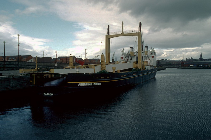 Some commercial port operations were still being undertaken from the Princes Dock in 1982. In this view the specialist heavy lift vessel Aberthaw Fisher is berthed in the Princes Dock Canting Basin, in front of Govan Town Hall, awaiting the delivery of a huge, specialist boiler from the Babcock factory in Renfrew. The boiler was to form part of the secondary cooling system at one of the Advanced Gas-cooled Reactor (AGR) nuclear power stations at Heysham or Hartlepool. Aberthaw Fisher and sister vessel, Kingsnorth Fisher, were operated on behalf of the Central Electricity Generating Board by James Fisher of Barrow-in-Furness.