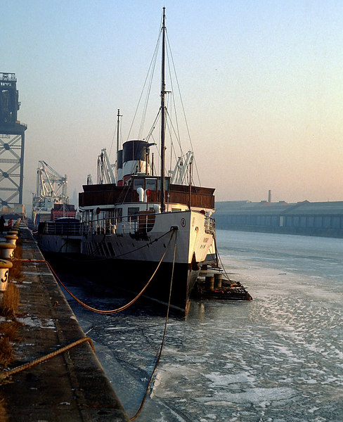 In January 1982, Glasgow and the West of Scotland experienced its most prolonged period of deeply sub-zero temperatures for many years. Temperatures remained around -20oC for almost 3 weeks and the River Clyde had a thick covering of ice, from bank to bank, as far downriver as Govan. This view shows Waverley, with the ferry Sound of Islay and a specialist heavy lift cargo ship astern, frozen in.