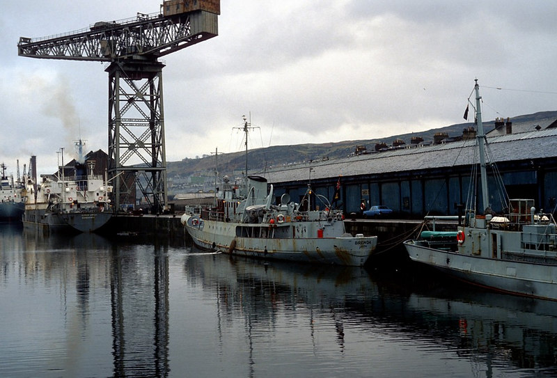 Along the road, Greenock's James Watt Dock was a busy place in 1982. In this view there is a Booker Line ship discharging a cargo of raw sugar at the far end of the dock which was also the base of the Scottish Office's fisheries protection cutters at that time.  Second from the left in this view is the FC Brenda and the stern section of the veteran FC Vigilant can also be seen.