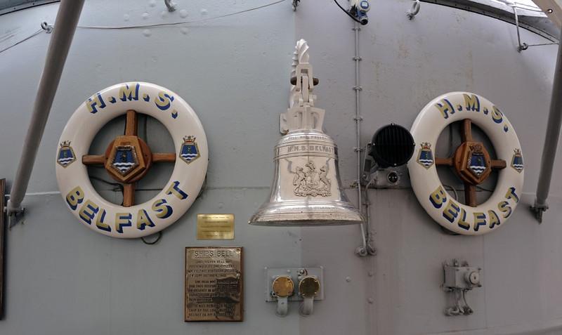 HMS Belfast, London, 3 September 2013: Ship's bell and badges.
