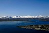 Tromso, 10 June 2008.  Looking west over southern Tromso.  Tirpitz was moored south (left) of the large island in the right distance when she was sunk by RAF Lancasters on 12 November 1944.  The snow covered mountains are a reminder that Tromso is north of the Arctic Circle.