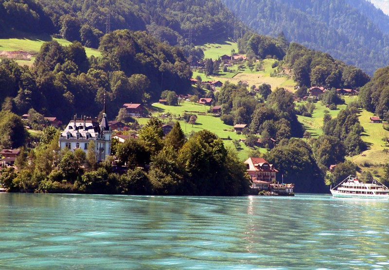 A more distant view astern from paddle steamer Lotschberg to Iseltwald with motor vessel Brienz approaching the pier
