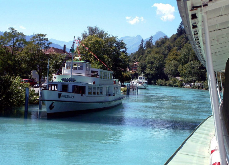 The view from paddle steamer Lotschberg as sge steams stern-first up the River Aare from Lake Brienz to Interlaken Ost with motor vessel Interlaken and another member of the BLS (Bern-Lotschberg-Simplon Railway) fleet moored by the riverside.